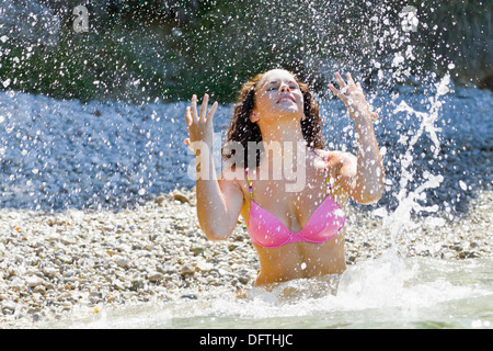 Throwing water upwards young woman standing in the shallow sea - Stock Photo