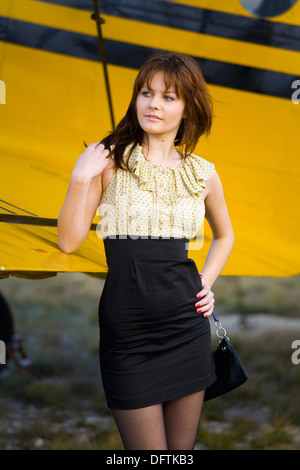 Fanciful young woman is waiting besides Yellow biplane airplane - Stock Photo