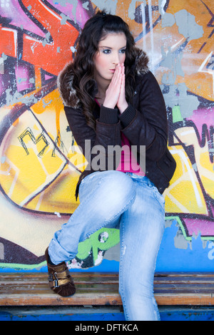Pretty young woman standing on the wooden bench before a colorful wall - Stock Photo