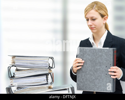 Thoughtful young businesswoman in front of a pile of folders - Stock Photo