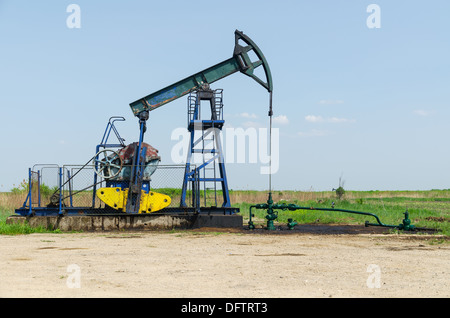 Oil Well Machine in Field on Clear Sunny Day, horizontal shot - Stock Photo