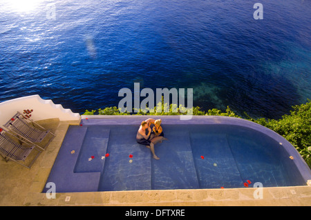 Couple relaxing in swimming pool at The Point (Private Villa) with the South Pacific Ocean in the background, Vatulele - Stock Photo