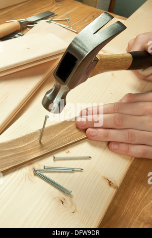 hammer nails in hardwood metal hammer and nails on wooden board stock photo royalty free