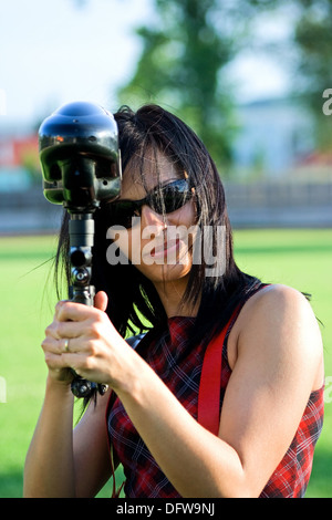 Female paintball player aiming the marker - Stock Photo