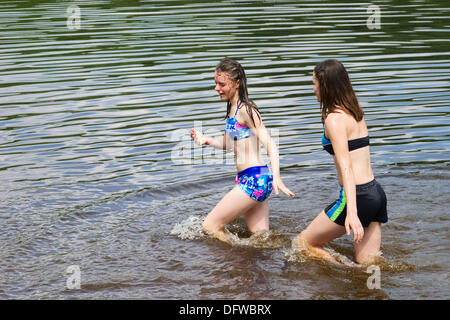 Teenage sisters, both in bathing suits, playing together at a lake in Connecticut, USA. - Stock Photo