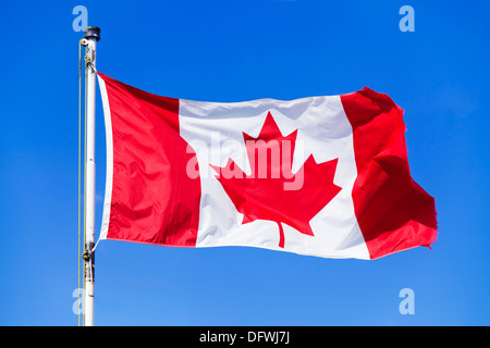 Canadian flag on a flagpole against a blue sky background no clouds canadian rockies canada - Stock Photo