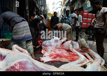 BANGLADESH Dhaka, Islamic Festival of Sacrifice Eid al-Adha, muslims slaughter animals on the road and distribute - Stock Photo