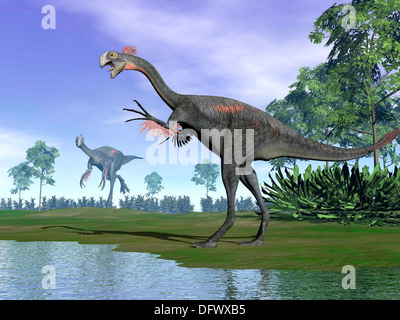 Two Gigantoraptor dinosaurs standing in nature with trees next to water. - Stock Photo