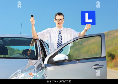 Happy young man posing near his car, holding a L sign and key after having his driver's licence on a road - Stock Photo