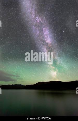 Aurora borealis and Milky Way above Fish Lake, Whitehorse, Yukon, Canada. - Stock Photo