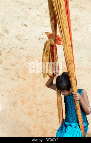 Young indian village girl playing on a swing made from a for Swingvillage
