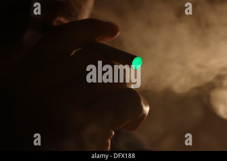 A person smoking an electronic cigarette - Stock Photo