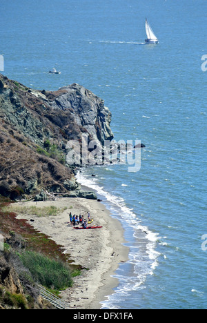 kayakers beach kayaks on remote cove on Angel Island state park - Stock Photo