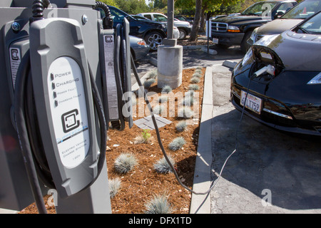 EV charging stations with plug-in electric car plugged in to charge its batteries in at a company parking lot - Stock Photo