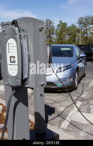 Plug-in electric car plugged into EV charging stations to charge its batteries in a workplace parking lot - Stock Photo