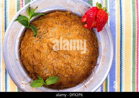 Turkish dessert kunefe isolated on a picnic cloth with mints and sliced strawberry - Stock Photo