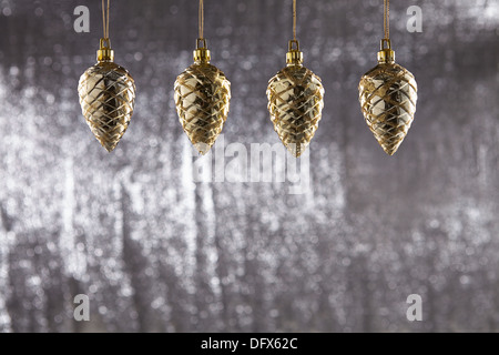 A group of christmas decoration pine cone hanging Against Silver glitter background with Shallow depth of Field - Stock Photo