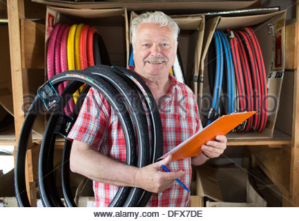 Old man working in a tire shop - Stock Photo