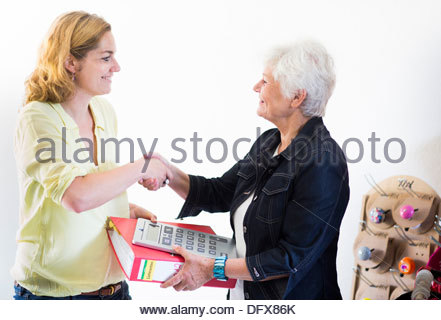 Mid adult woman shaking hands with an old woman - Stock Photo