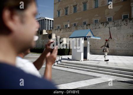 Tourists watching the changing of the guard ceremony at the Tomb of the Unknown Soldier in Syntagma Square in Athens, - Stock Photo