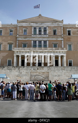 Tourists watching the changing of the guard ceremony at the Tomb of the Unknown Soldier in front of the Greek Parliament - Stock Photo