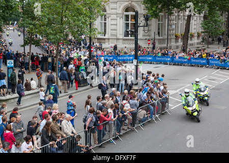 Spectators look on as police outriders lead the riders through the streets of London during the Tour of Britain - Stock Photo