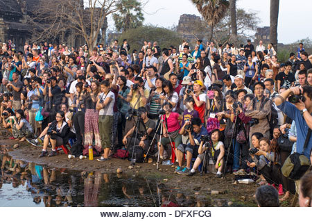 Tourists waiting to photograph the Sunrise at Angkor Wat. Cambod - Stock Photo