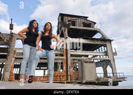 Two girlfriends are posing next to a derelict building remains of a torpedo testing station in Rijeka, Croatia - Stock Photo