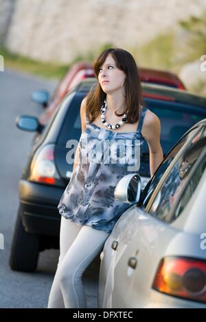 Pretty young woman and parked cars - Stock Photo