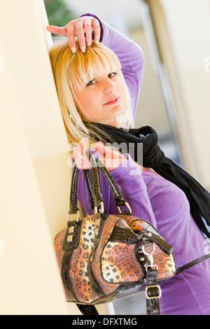 Fashionable young woman is adjusting hair - Stock Photo