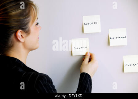 20 yr old young woman looking at sticky notes on wall - Stock Photo
