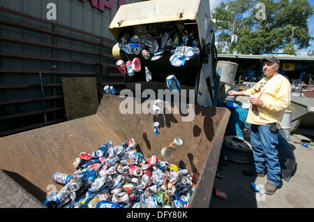 Male employee uses machine to crush aluminum cans at a metal recycling company in Texas - Stock Photo