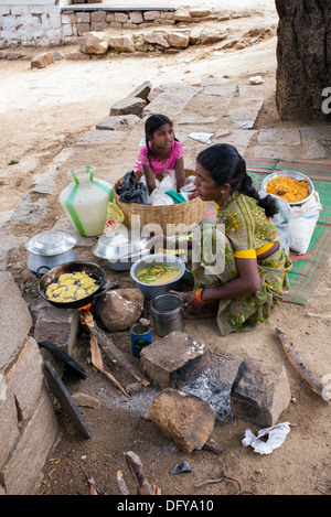 Indian woman cooking deep fried baattered chilli on the street in a rural indian village. Andhra Pradesh, India - Stock Photo