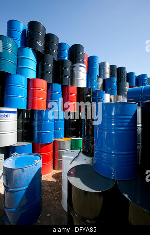 Metal oil barrels brought into scrap metal recycling yard in Texas - Stock Photo
