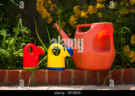 North West London suburban garden three 3 plastic kids childrens watering can cans two childrens red yellow red - Stock Photo