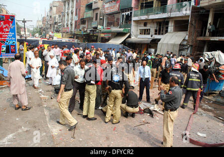 Police officials and people busy in rescue work at the site after strong bomb explosion outside a Biryani restaurant - Stock Photo
