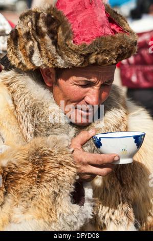 Kazakh eagle hunter drinking milk tea in the Altai Region of Bayan-Ölgii in Western Mongolia - Stock Photo