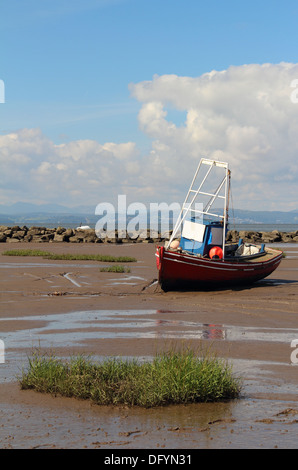 A red, white and blue fishing boat resting on the sands of Morecambe Bay during low tide. - Stock Photo