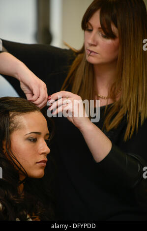 Manchester, UK. 10th Oct, 2013. A young woman has her hair styled prior to the start of a catwalk event taking part - Stock Photo