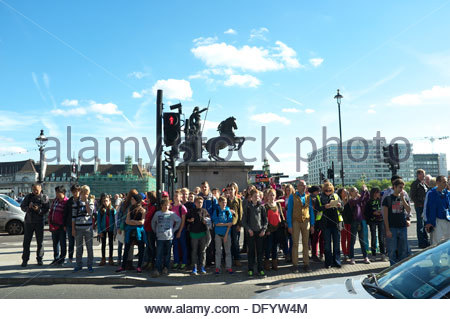 A school party of children waiting to cross the Embankment at Westminster Bridge, with the statue of Boadicea behind - Stock Photo