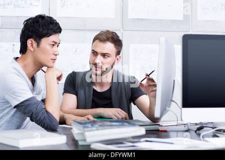 Young adults discussing in office - Stock Photo