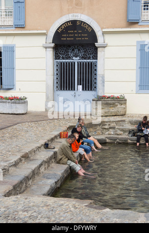 France, Ariege, Pyrenees - Ax-les-Thermes spa town and ski resort. Sitting with feet in the hot spring sulphur pool. - Stock Photo
