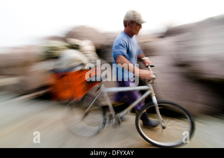 local fisherman riding bicycle at the 'molhes' in Rio Grande city, Rio Grande do Sul state, Brazil. slow shutter - Stock Photo