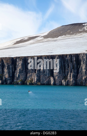 Zodiac approaching the Brunnich's Guillemot breeding colony at Alkefjellet, Svalbard Archipelago - Stock Photo