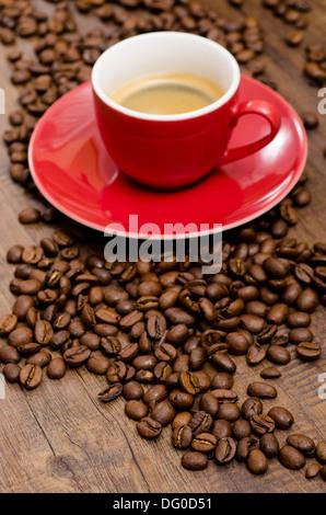 Arabica Kaffebohnen und rote Espressotasse auf einem dunklem Tisch aus Holz - Stock Photo