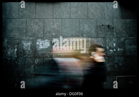 Blurred silhouettes of people passing through a wall - Stock Photo