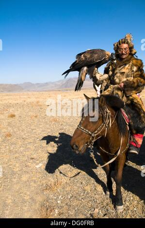 A Kazakh eagle hunter from the Altai region of western Mongolia riding his horse. - Stock Photo