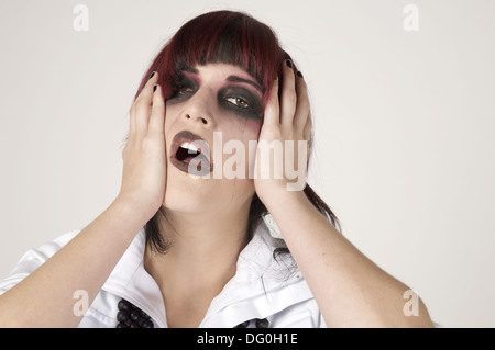 Rocker girl with heavy makeup and tear running down looking desperate and depressed - Stock Photo