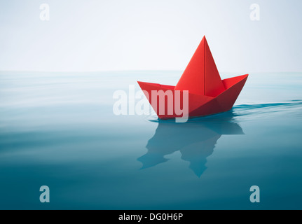 red paper boat sailing on water with waves and ripples - Stock Photo