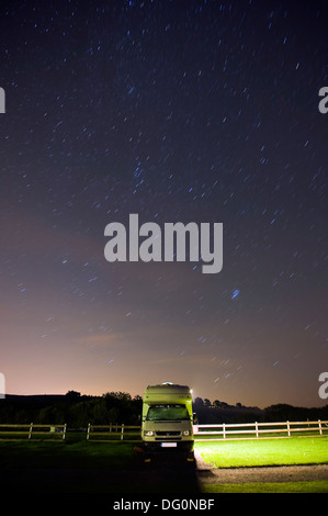 Moving stars in the night sky above a camper van in Dorset, UK - Stock Photo